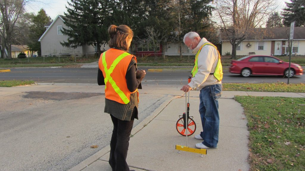 Two field staff wearing safety vests take measurements of a sidewalk using a slope meter and measuring wheel.