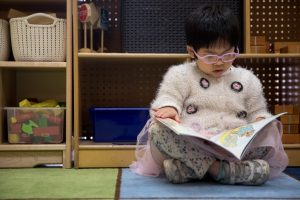 A child reads a book in a classroom