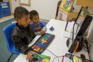 Two children working at a computer station