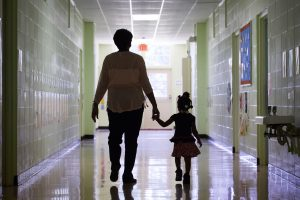 A teacher walks with a student down a hallway