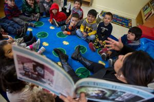 A volunteer parent reads for a classroom of children