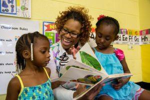 A parent volunteer reads to children