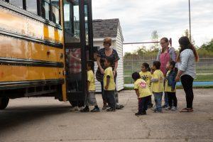 Children await to board a bus