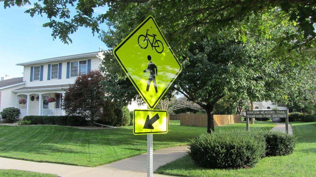 A bicycle and pedestrian crossing sign marks a trail crossing in Champaign.