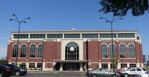 A view of the Illinois Terminal, a large red brick building with arched windows, with its front doors and parking lot in the foreground and bus shelter and apartment buildings visible in the background.