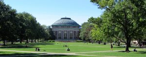 A view across a quad at the University of Illinois. Students sit on the grass alone or in groups. Paths crisscross the quad. Many trees line the edges of the quad, and a domed university building, Foellinger Auditorium, is visible at the far end.