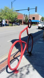A red bicycle rack shaped like a person on a bicycle in motion, anchored to a sidewalk with brick detail beside a downtown street.