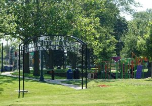 """A park with many trees, a metal gateway with a sign reading """"Hazel Park: Dedicated to Hazel Iungerich, Champaign Park District,"""" and a colorful playground beyond the gateway."""