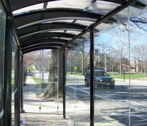 An interior view of a Champaign-Urbana Mass Transit District bus shelter, the two-lane street beyond the shelter, and campus buildings in the distance.
