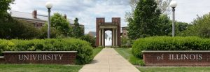 "Low brick fences on either side of a concrete path, with one side reading ""University"" and the other reading ""of Illinois."" Landscaping, campus buildings, trees, a columned brick archway and a fountain are beyond the brick fences."