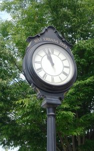 """A close-framed image of a dark blue outdoor clock with gold details, reading """"1833 Urbana 1993."""" There is a tree behind the clock, and the time is 10:57 a.m."""