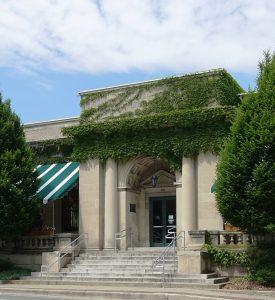 The steps and patio of the Urbana Free Library, a stone building partially covered with ivy and featuring columns and other architectural details and green-and-white striped awnings.