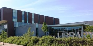 """The Champaign Public Library, a building featuring modern architecture, low-to-the-ground landscaping, and a large metal sign reading """"LIBRARY."""""""