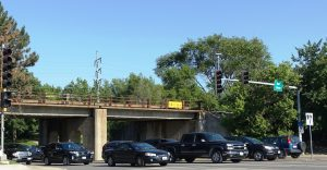 A multi-lane divided street entering an intersection, traffic lights, several cars approaching the intersection, and a railroad underpass beyond the cars.