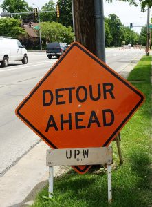 """An orange road sign reading """"Detour Ahead,"""" and part of a street and a construction zone beyond the sign."""