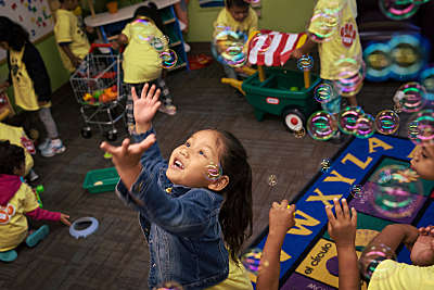 A girl reaches for bubbles in a Head Start classroom.