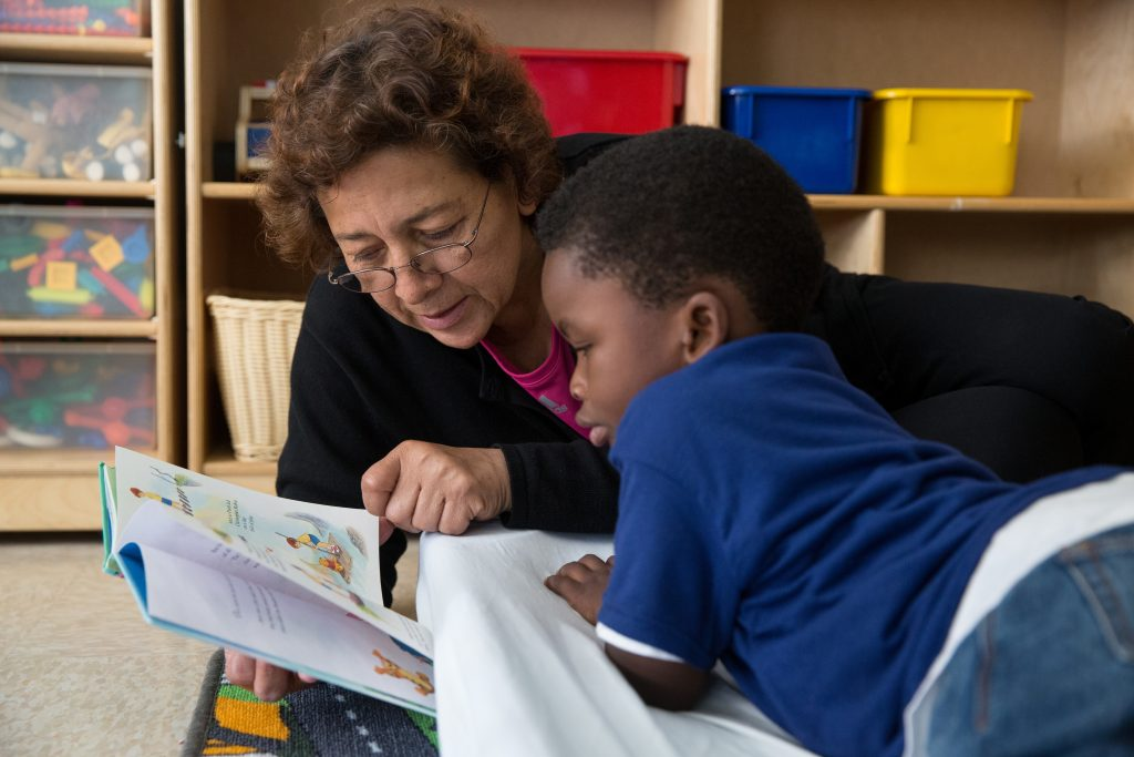 A teacher reads to a child
