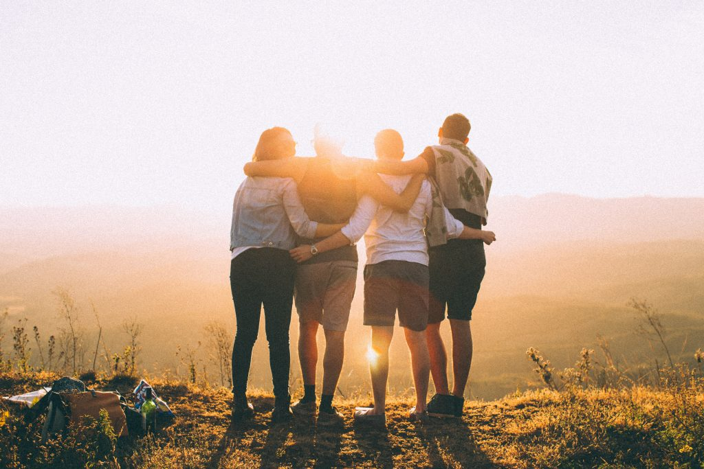 A group of people in a field watch the sun rise.