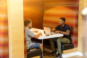 Two aspiring business owners make plans at a restaurant booth