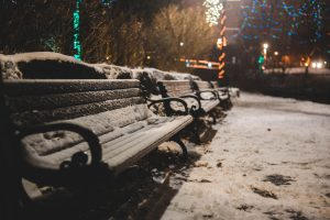 Snow-covered benches in a city park