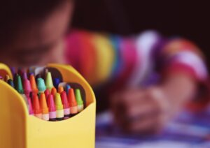 A preschool child coloring with crayons