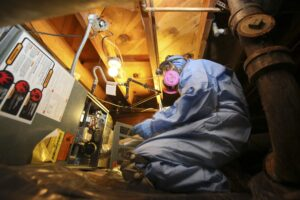 A Weatherization contractor working on a furnace